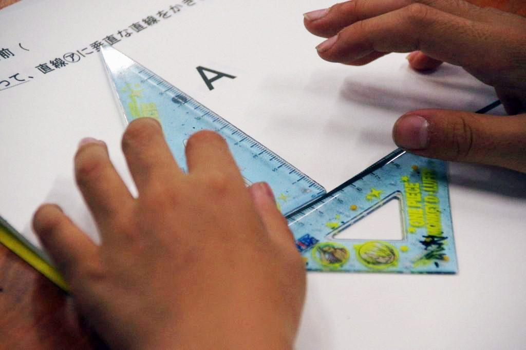 三角定規で算数を解いている子ども