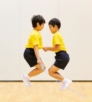 例1/互いに向かい合って跳びます。一人がなわを回し、二人でタイミングを合わせてジャンプします。