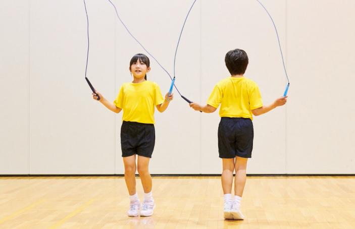 例2/横に前後反対向きに並んで、2本のなわの片方の持ち手を、左右逆の手で持ちます。一人は前回し、もう一人は後ろ回しの形で、同時になわを回して跳びます。