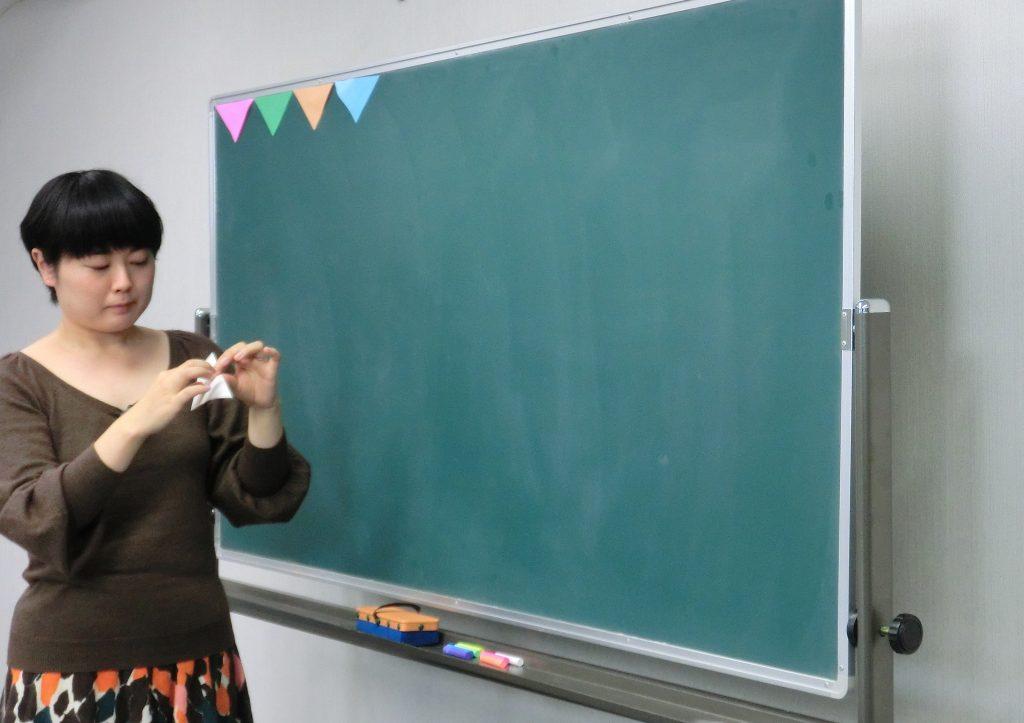 直角二等辺三角形になるように切った折り紙を、黒板の一番上に並べて貼っていきます。折り紙の裏に、輪にしたテープをつけて貼ると簡単です。