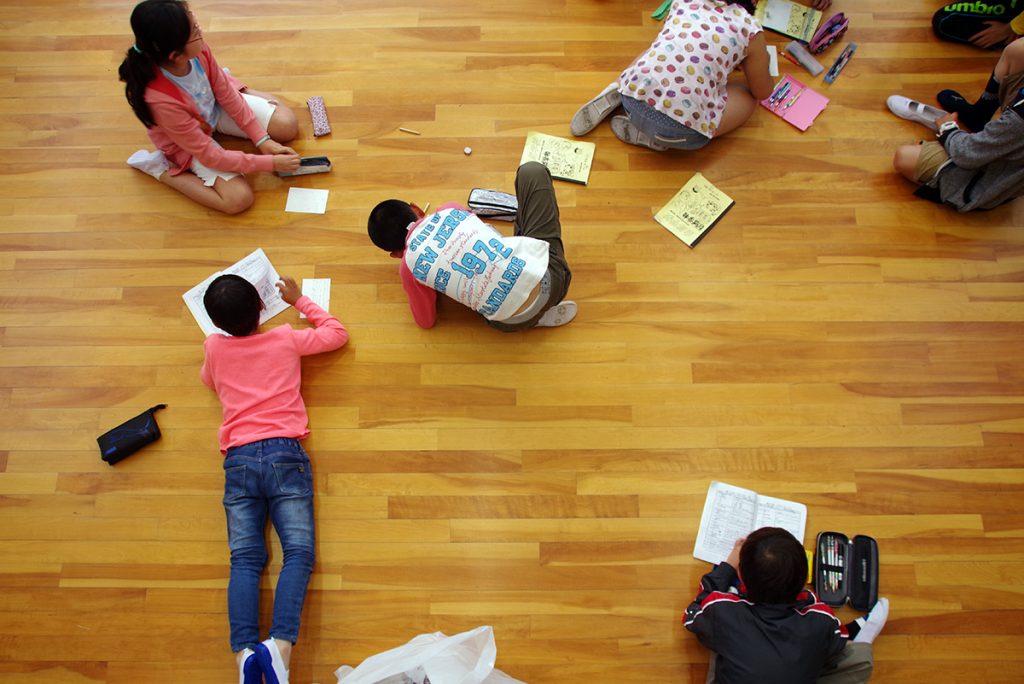 自由な体勢で勉強する児童