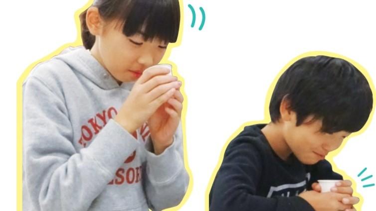 試飲用の液AとBの香りや味を確かめる子供たち