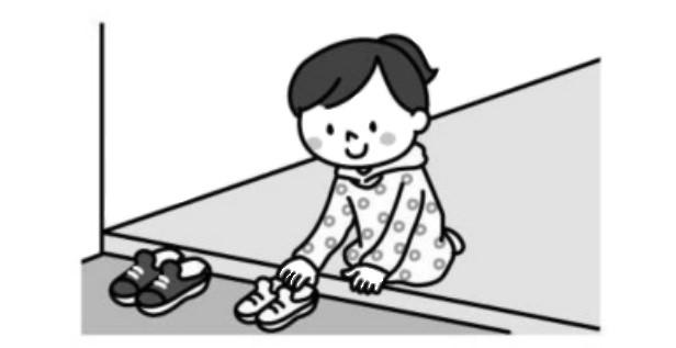 玄関で靴を揃える子供