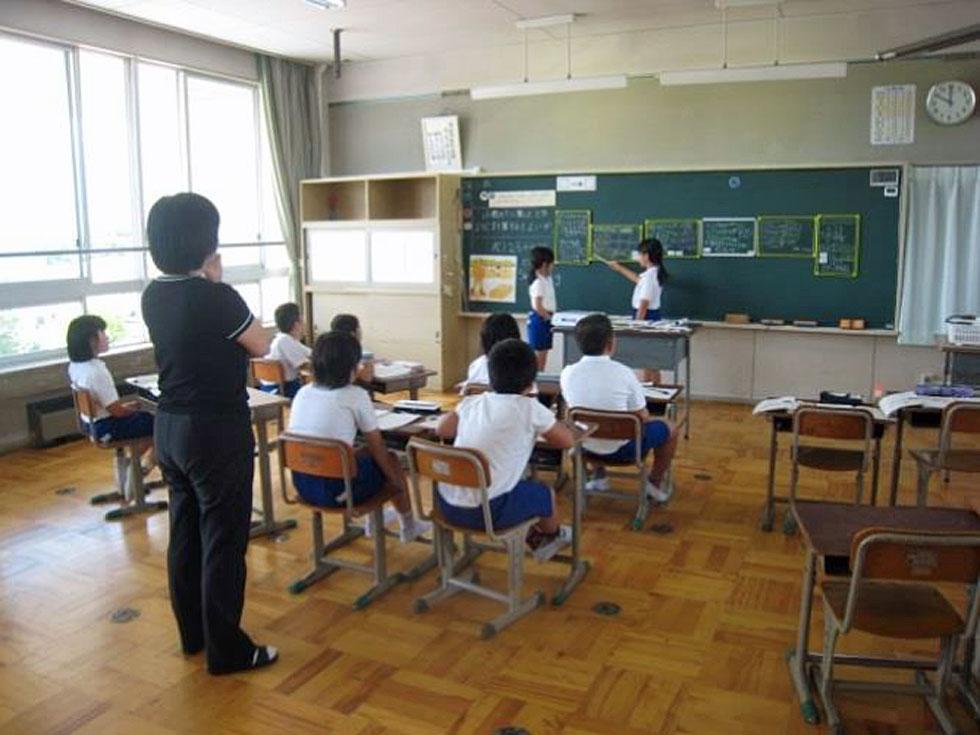教室の後方から子どもの学びを見守る教師の姿