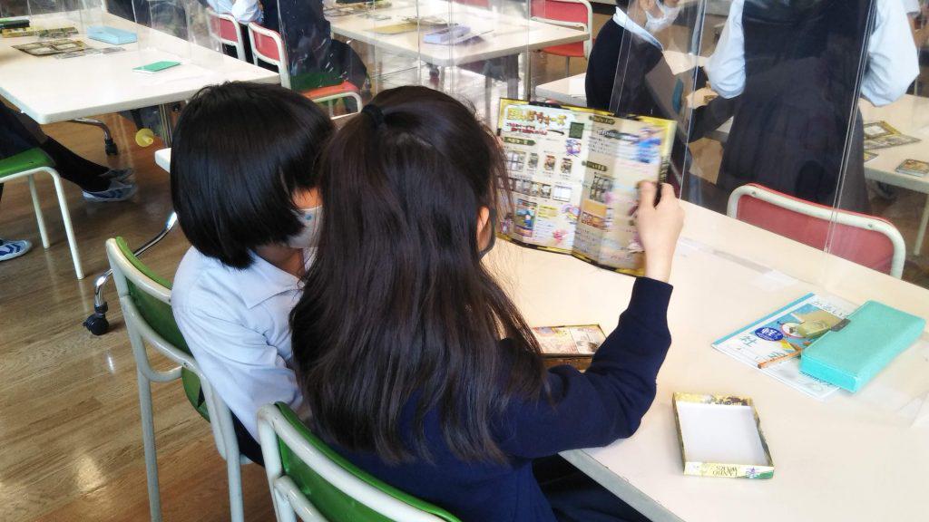 男女ペアとなり、「田んぼウォーズ」の説明書を読む子供たち。田んぼを増やす方法について、仲良く話し合う。