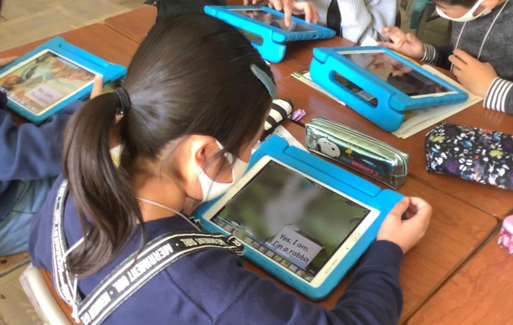 何度も音声を聞き、声に出して英語を練習する児童