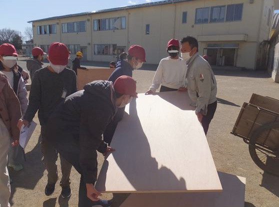 坂戸市の「木下材木店」の方に、ジャンピングボードの作り方を教えてもらう子供たち。