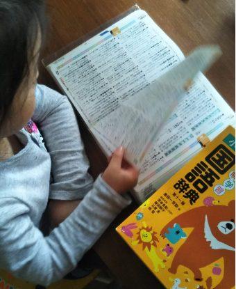 コトバトで 『例解学習国語辞典[第十一版]』 をめくり、言葉を探す子供。