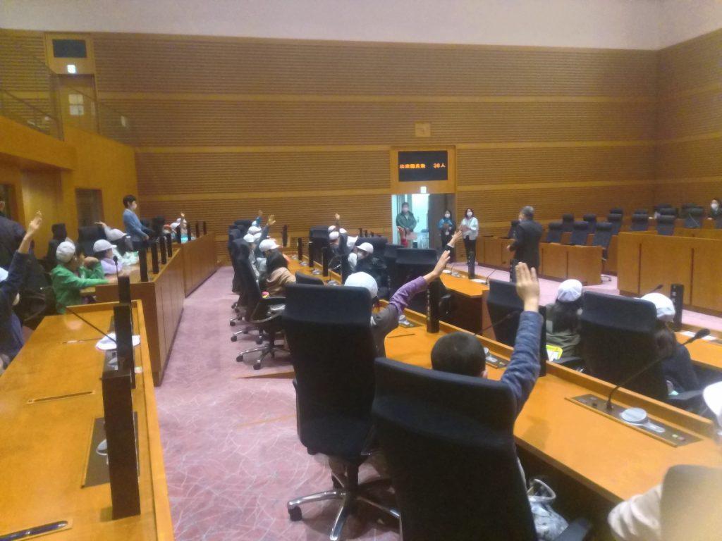 市議会議場の席に座ります。市役所の方が議題を提示し、議場の採決機能を用いて採決を体験します。
